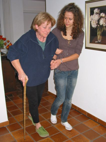A caregiver helps a woman walk in her home.