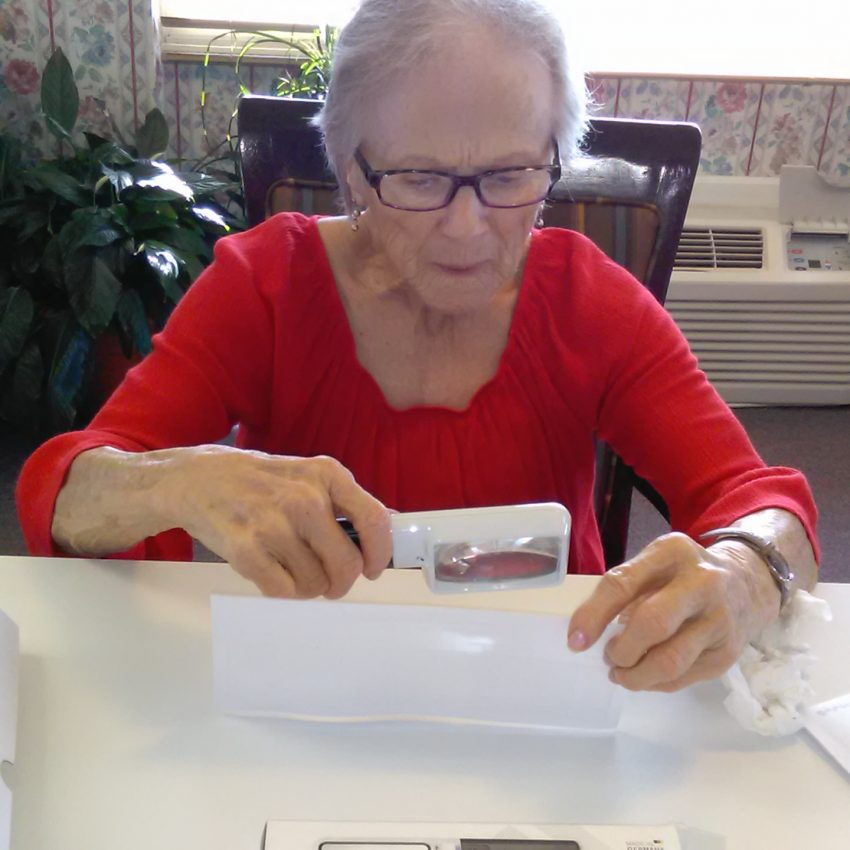 Roberta is trying out some assistive devices for low vision. We provide a demonstration room for people to try various devices so they can make an informed decision about which devices may make their lives easier.